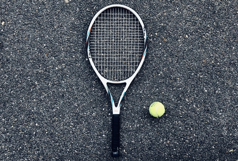 white tennis racket and green tennis ball