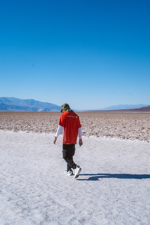 man wearing red and white shirt walking on sand