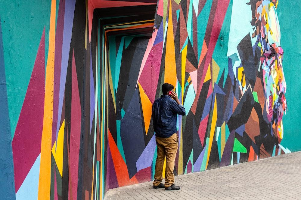 man wearing blue dress shirt and brown jeans standing beside of graffiti wall art
