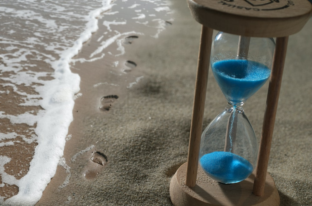 brown hourglass with blue sand on shore