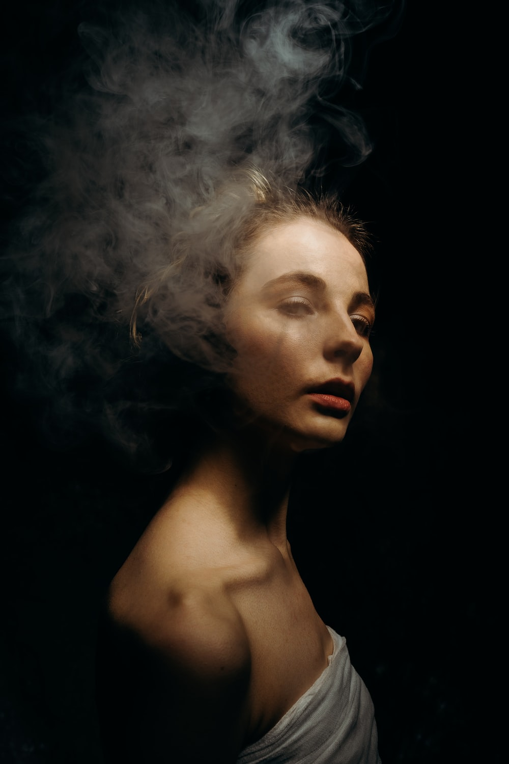female model in a white top and smoke