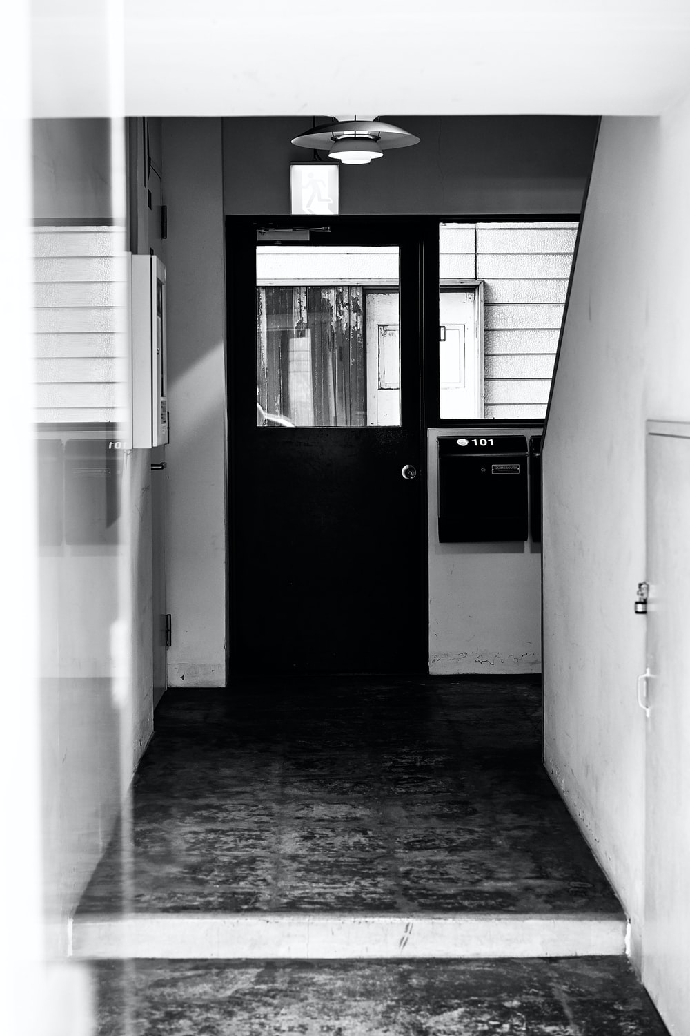 grayscale picture of a hallway with black door