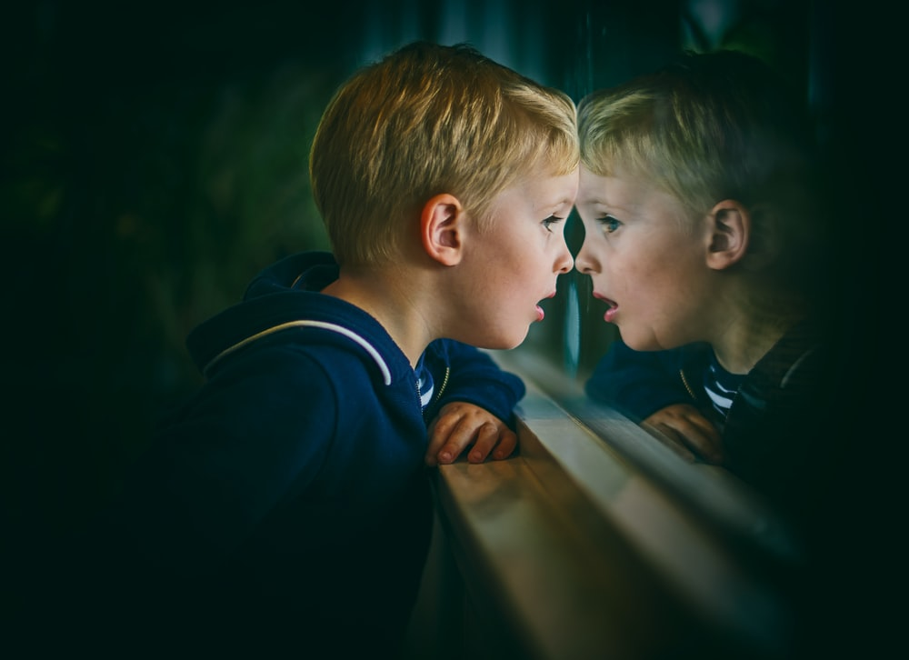 boy looking at window during night time