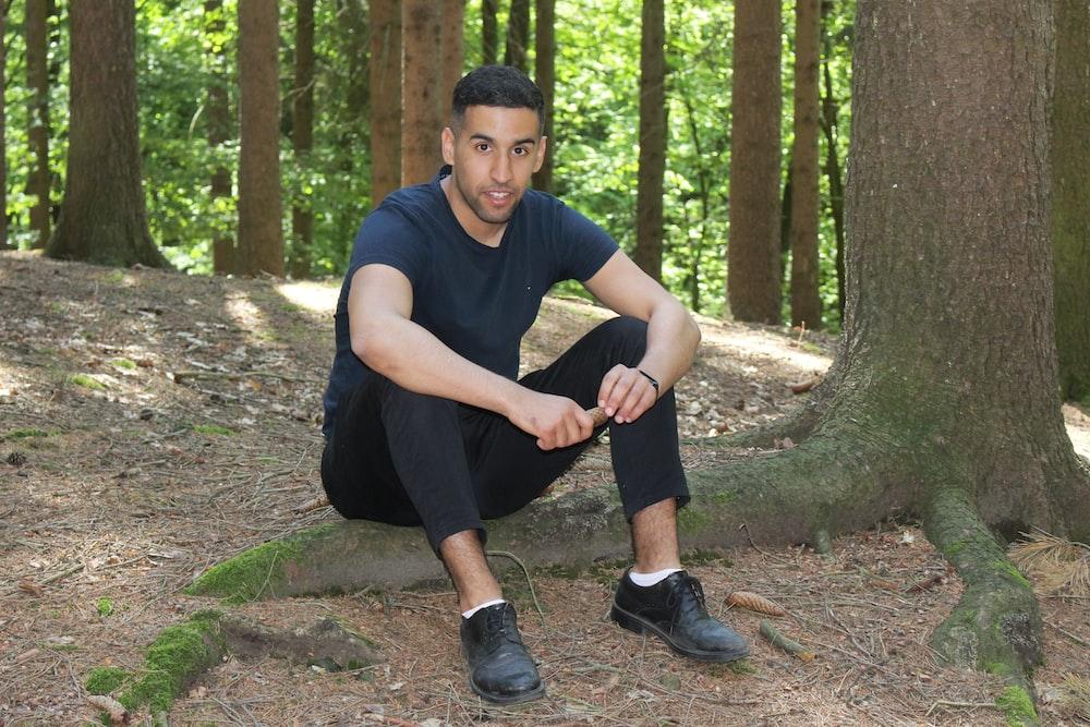 man sitting on tree roots