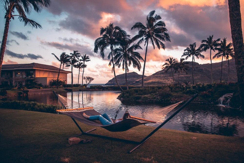person on brown hammock with steel base across body of water