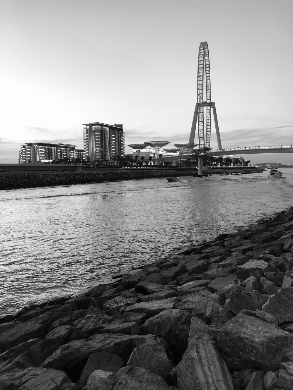 grayscale photo of body of water over bridge facing buildings