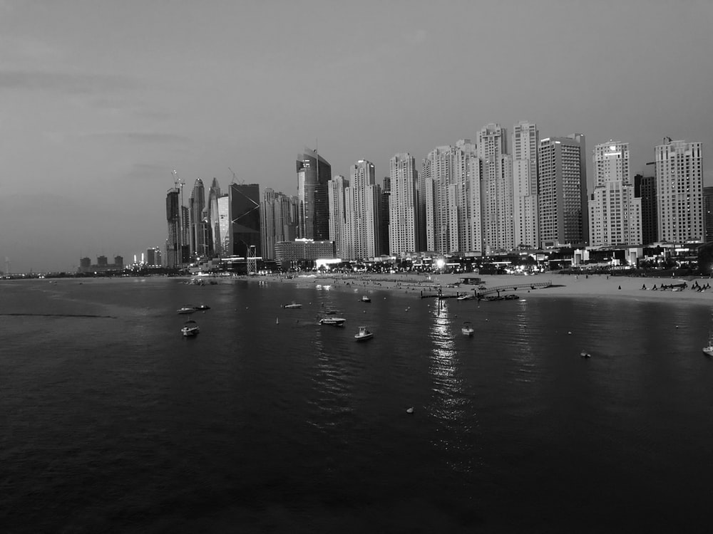 grayscale photography of city buildings beside beach