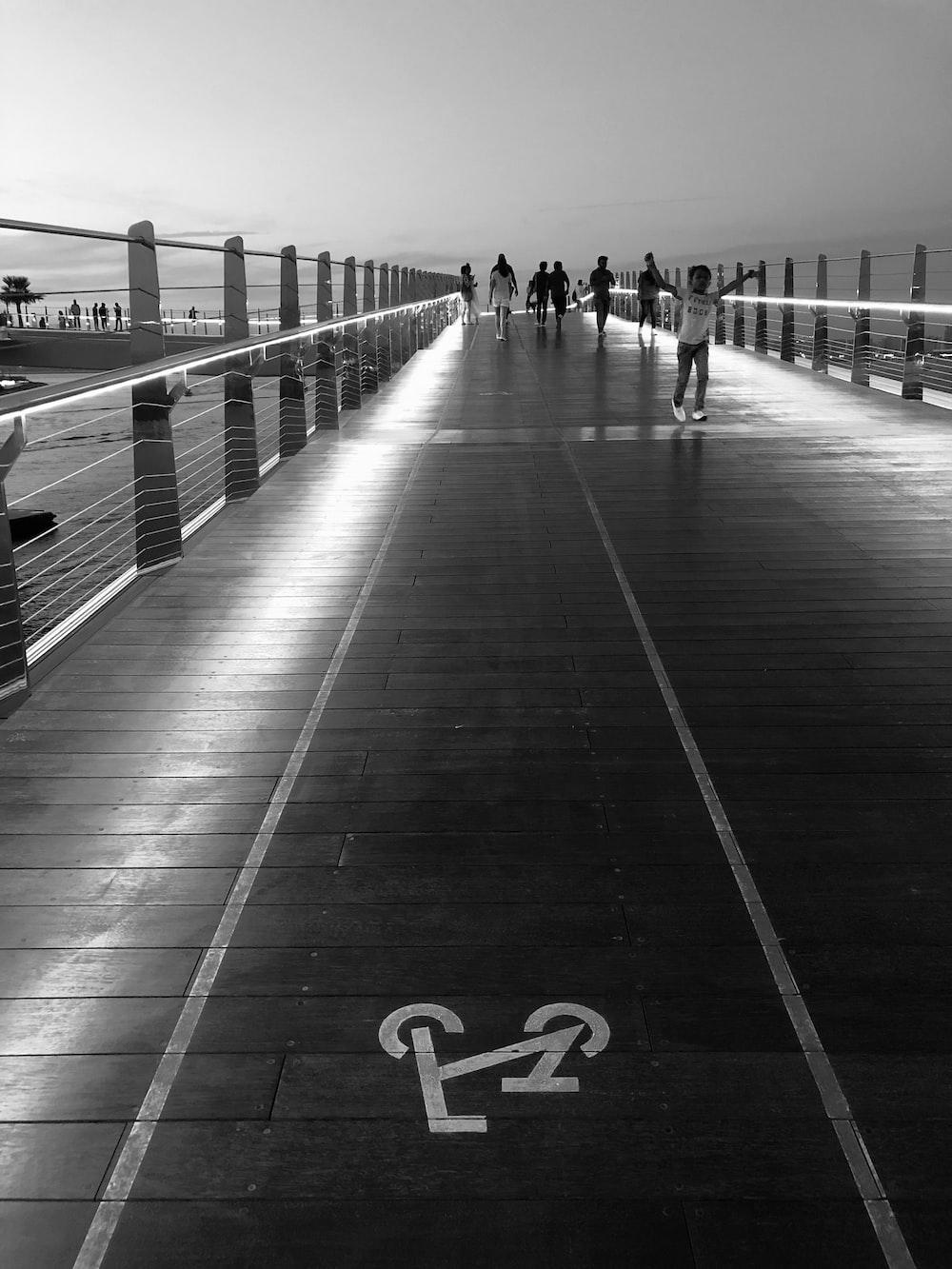 people standing and walking on bridge