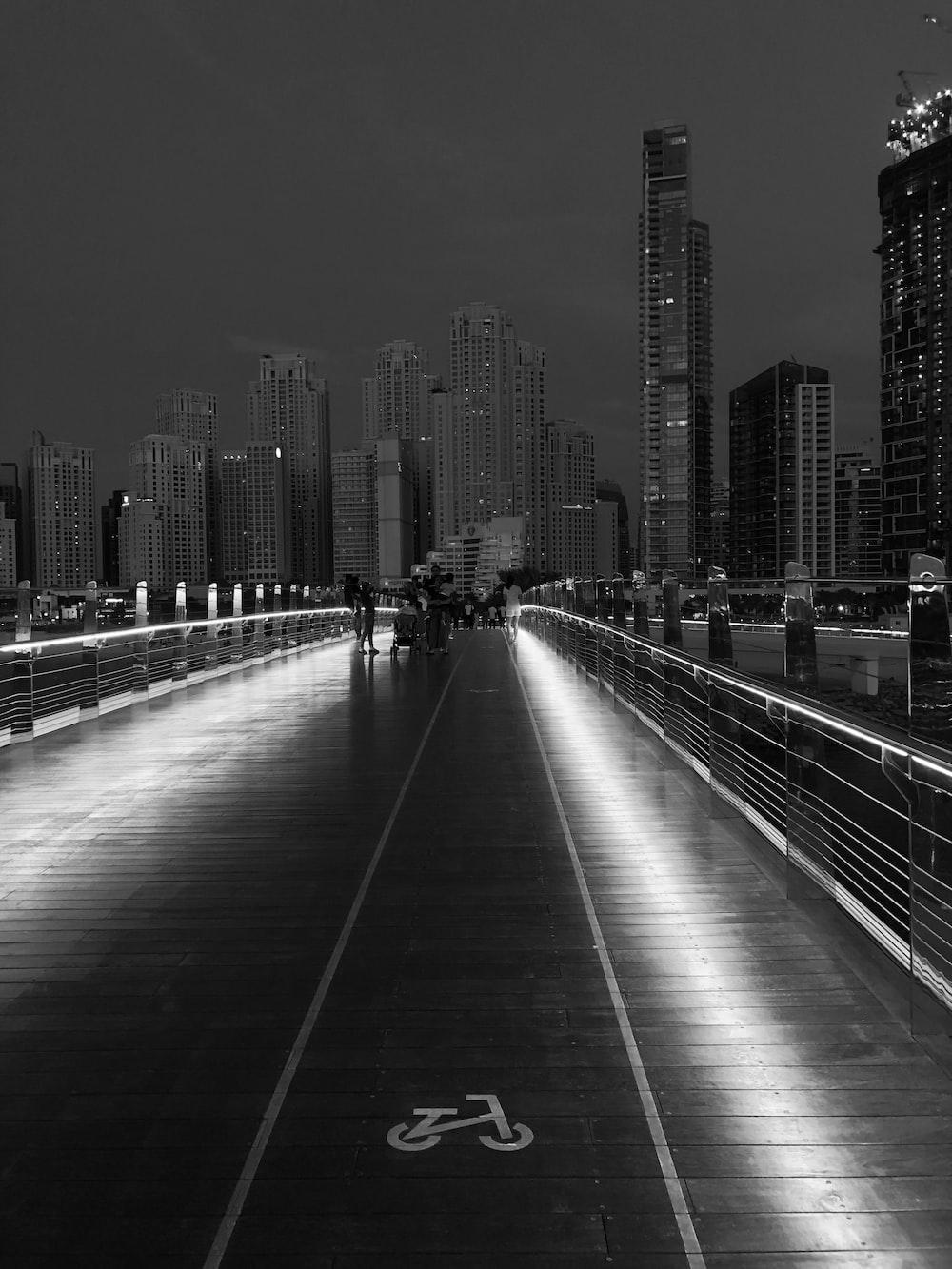 grayscale photo of bridge across city building