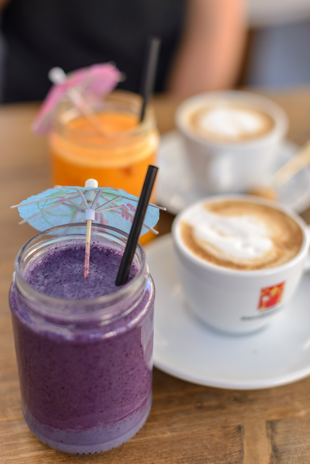 two orange and purple beverage in jar with small umbrella beside coffee latte