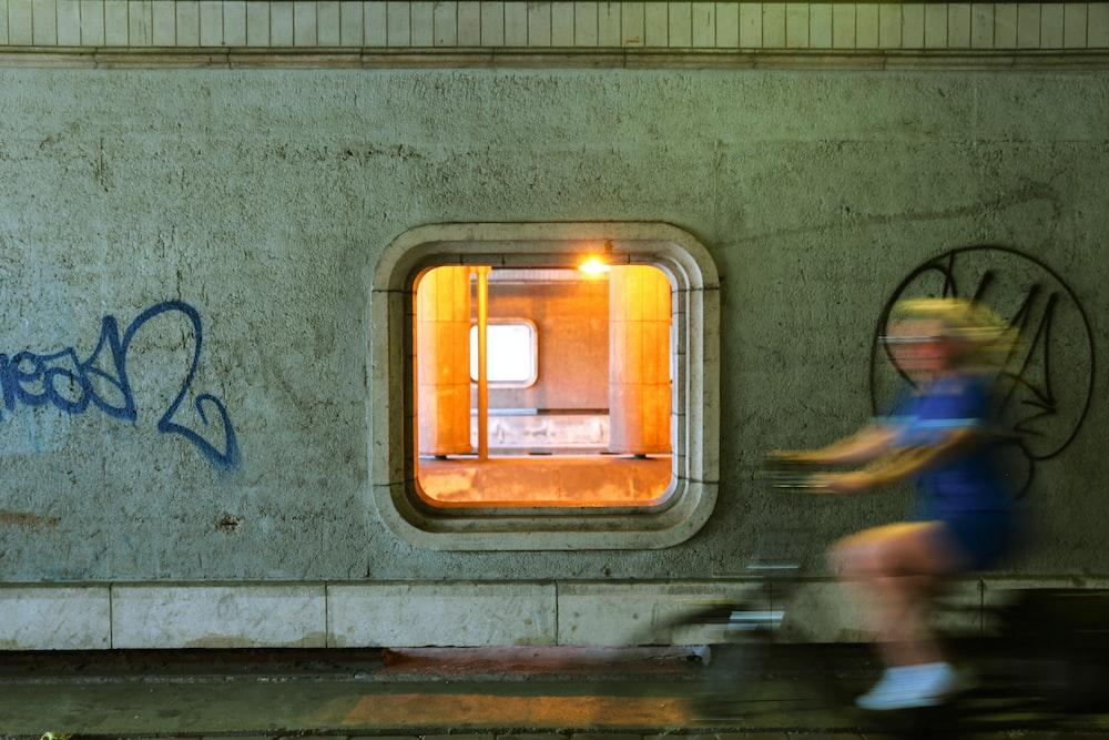 person cycling near concrete wall