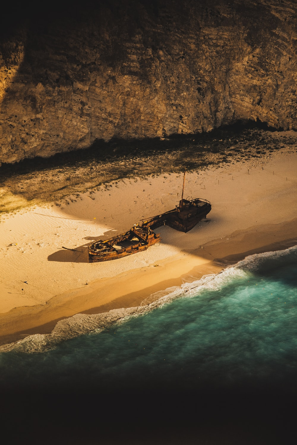 wrecked and abandoned ship on shore of an island during golden hour