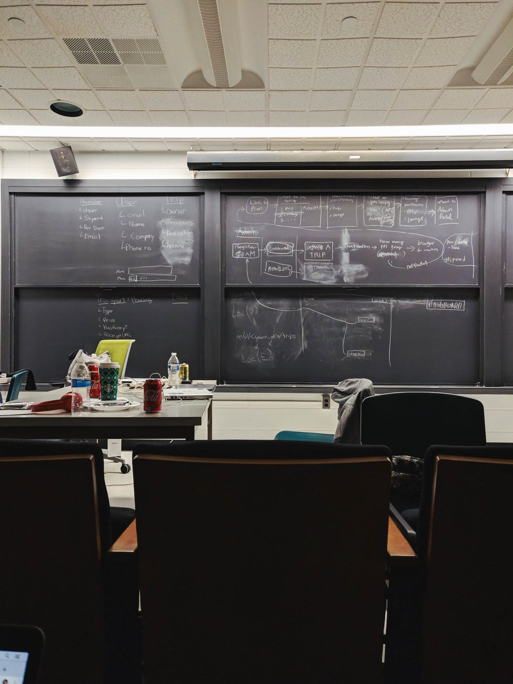 different can and cups on white table beside chalkboard inside building