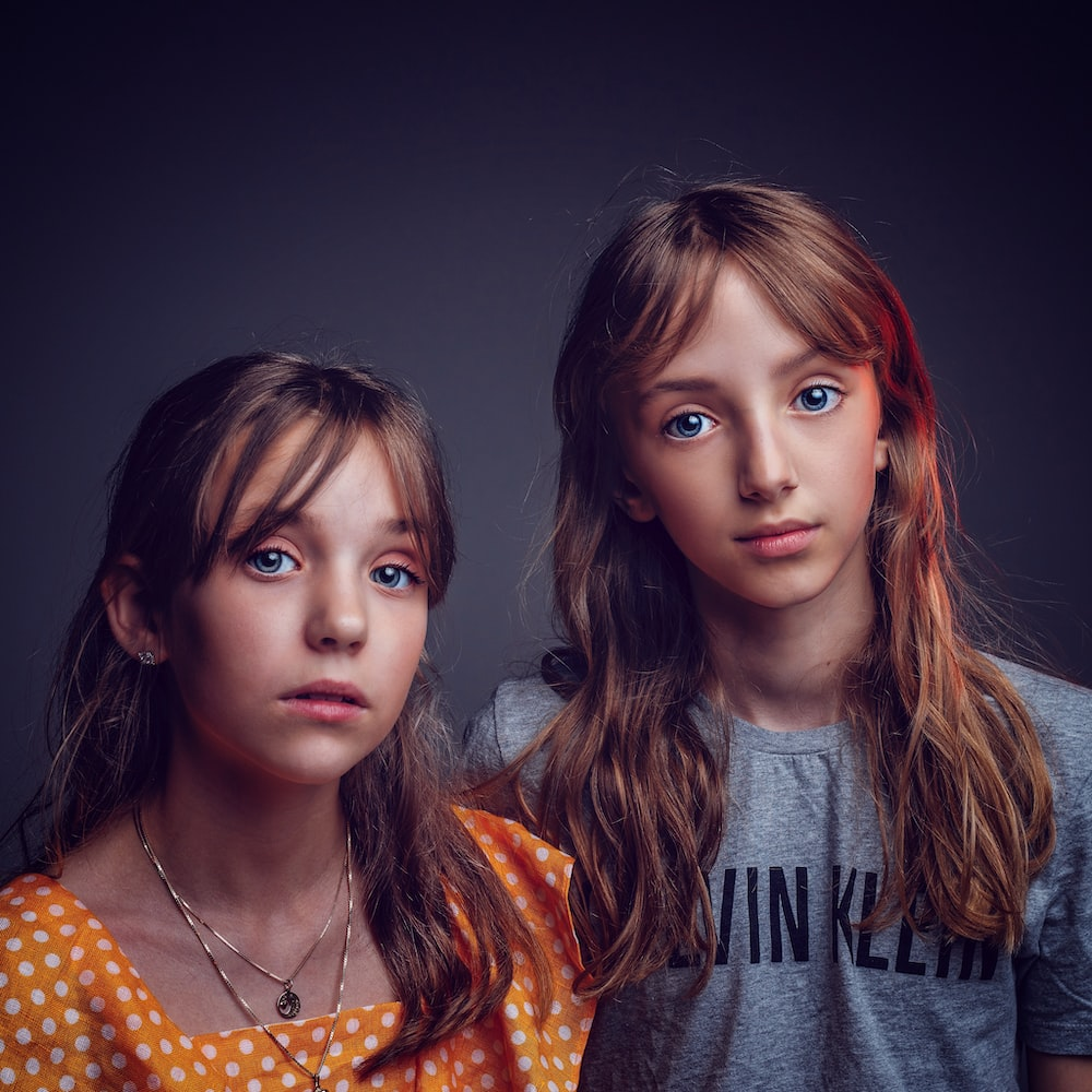 two girls in shirts posing for photo