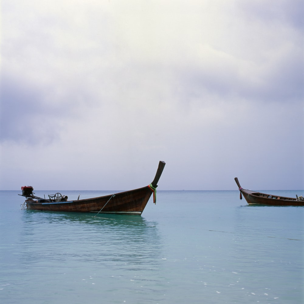 two brown motorboat on body of water