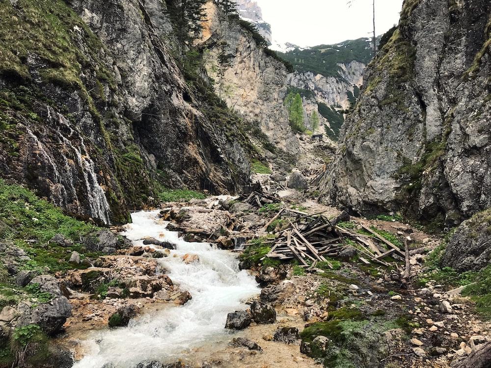 river between mountain during daytime