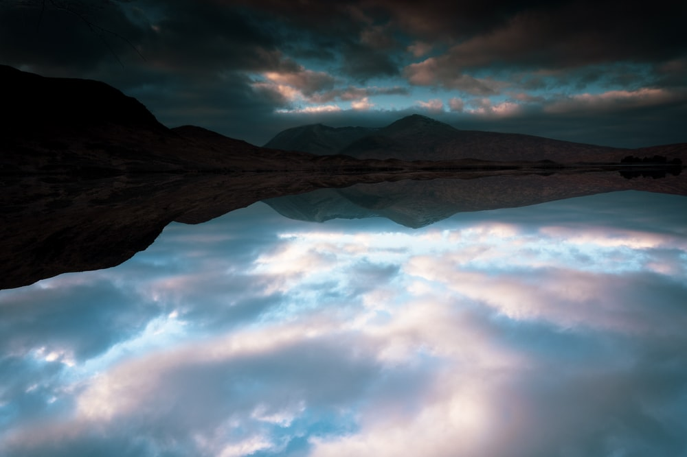 reflection of dramatic clouds on calm body of water