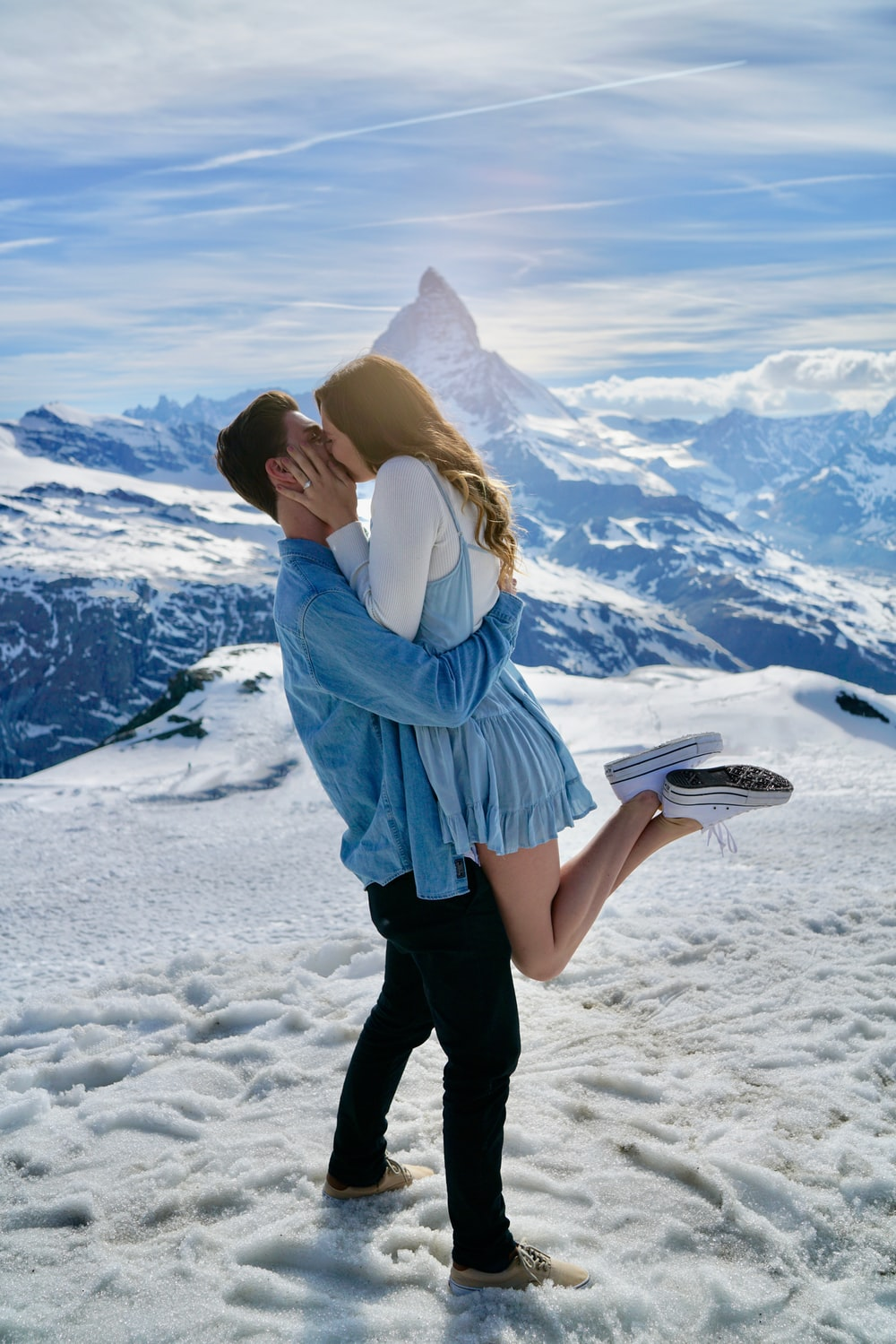 man carrying woman and kiss under clear blue sky