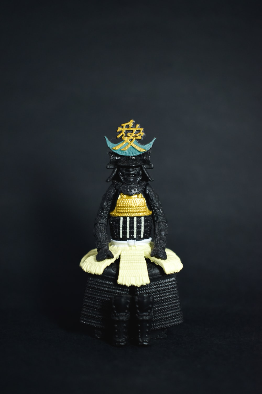 black, yellow, and blue deity figurine