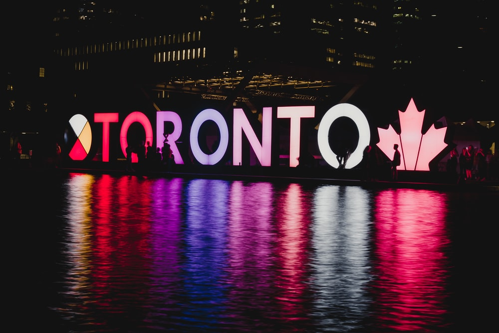 Toronto LED signage beside body of water during night