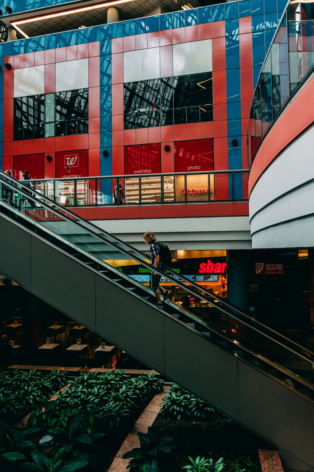 person carrying backpack on escalator photo