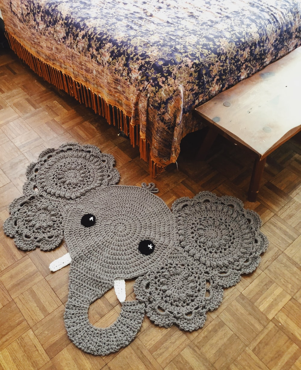 black and gray elephant plush toy on brown wooden table