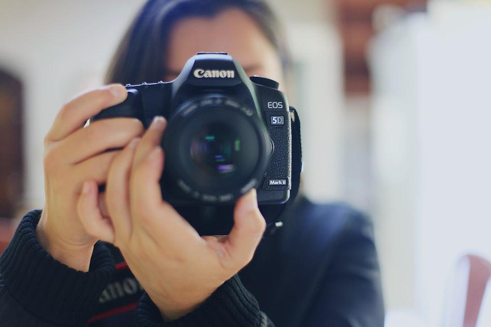 woman using black Canon DSLR camera