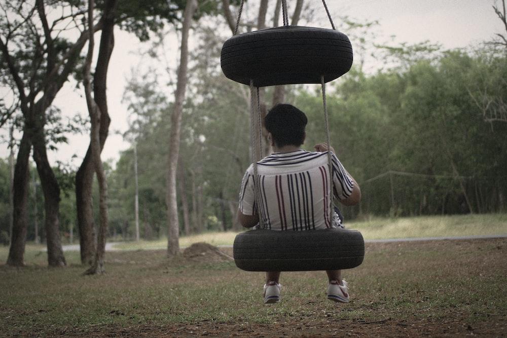 man sitting on tire swing