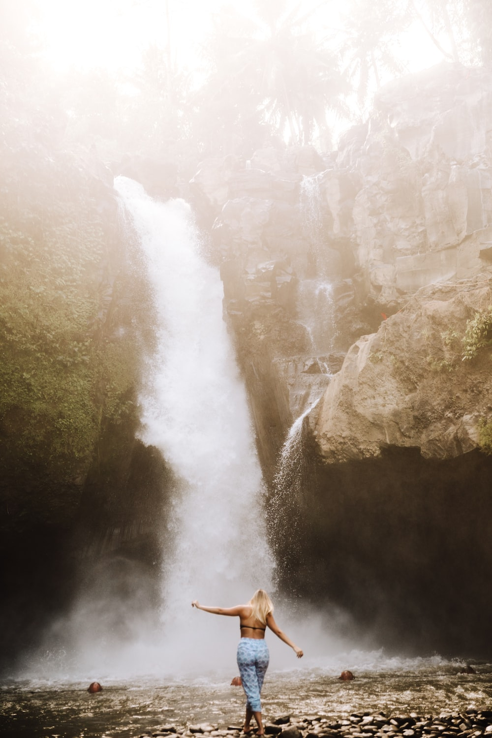 woman standing in front of plunge waterfall