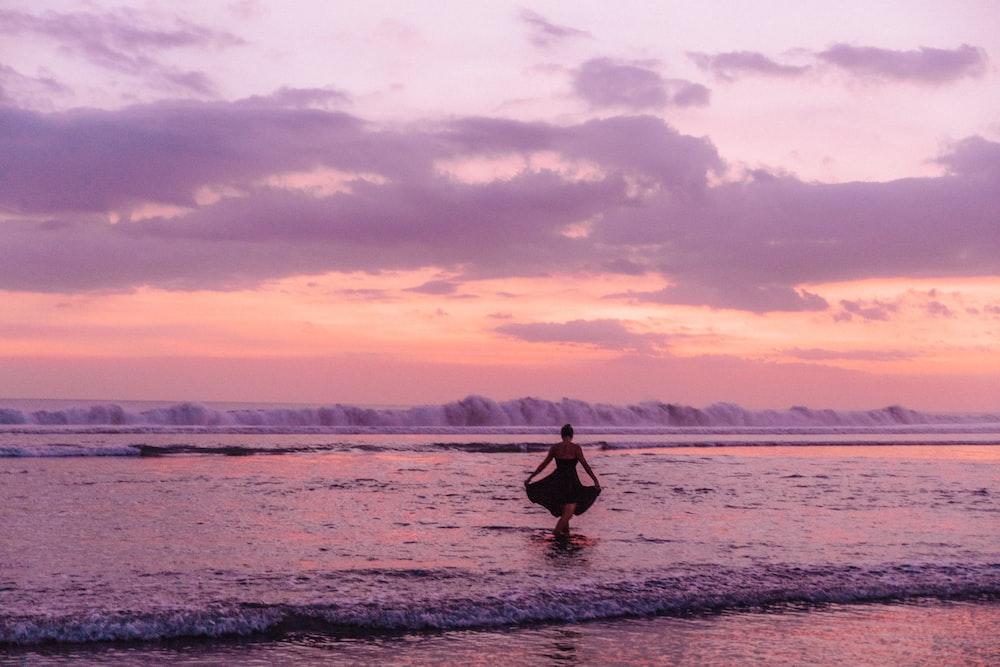 woman wearing dress walking towards the ocean during golden hour