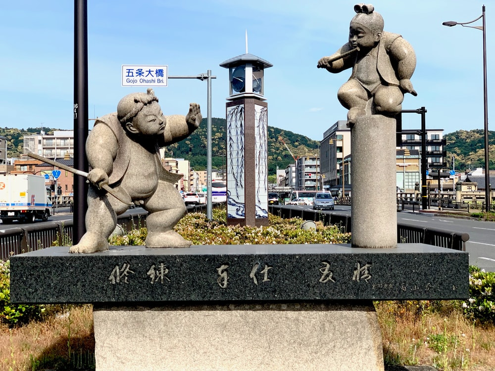 two grey men fighting ceramic statues