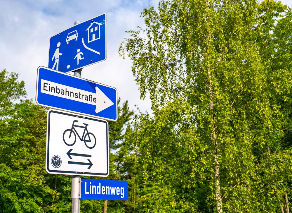 blue and white signage near trees during daytime