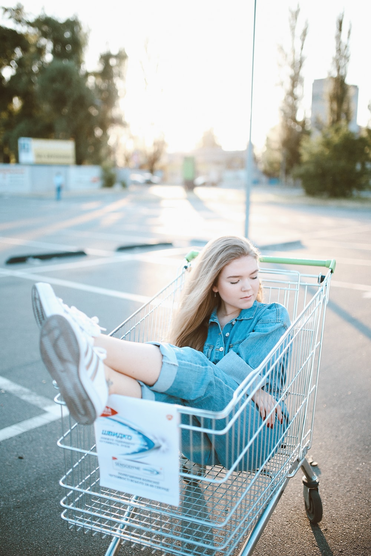 woman sitting in shopping cart
