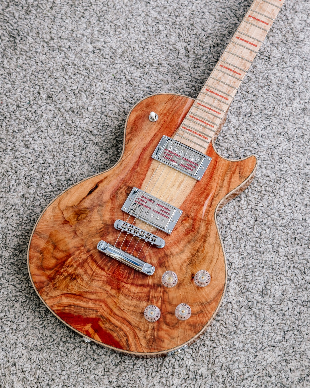 A custom made Les Paul guitar with natural red colour from the carob wood used by the guitar maker. An art piece from a French guitar maker.