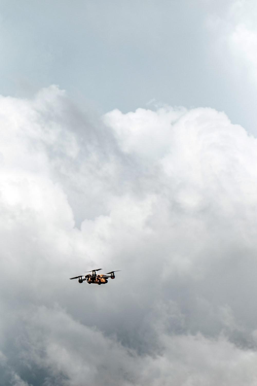 black drone under white clouds