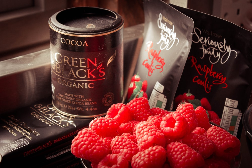 Cocoa Green & Black's can and bunch of raspberries