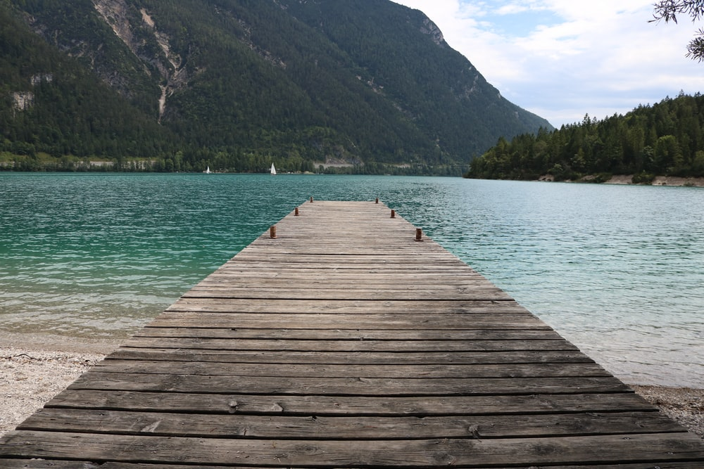 brown wooden dock towards body of water during daytime