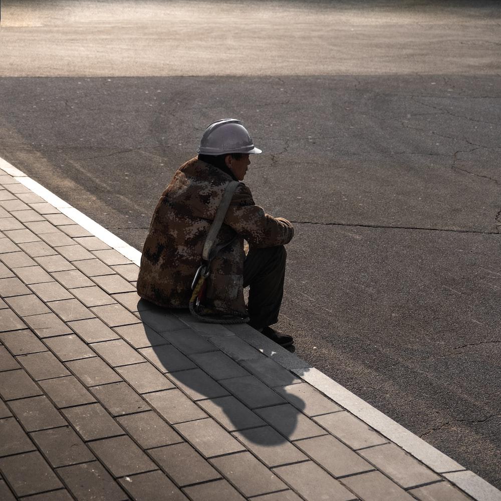 man sitting beside road