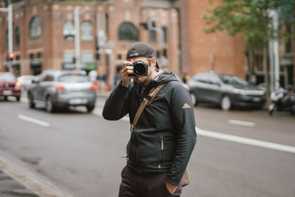 man wearing black hoodie holding camera while taking a picture