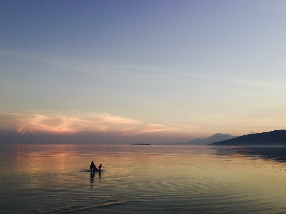 person on body of water during golden hour