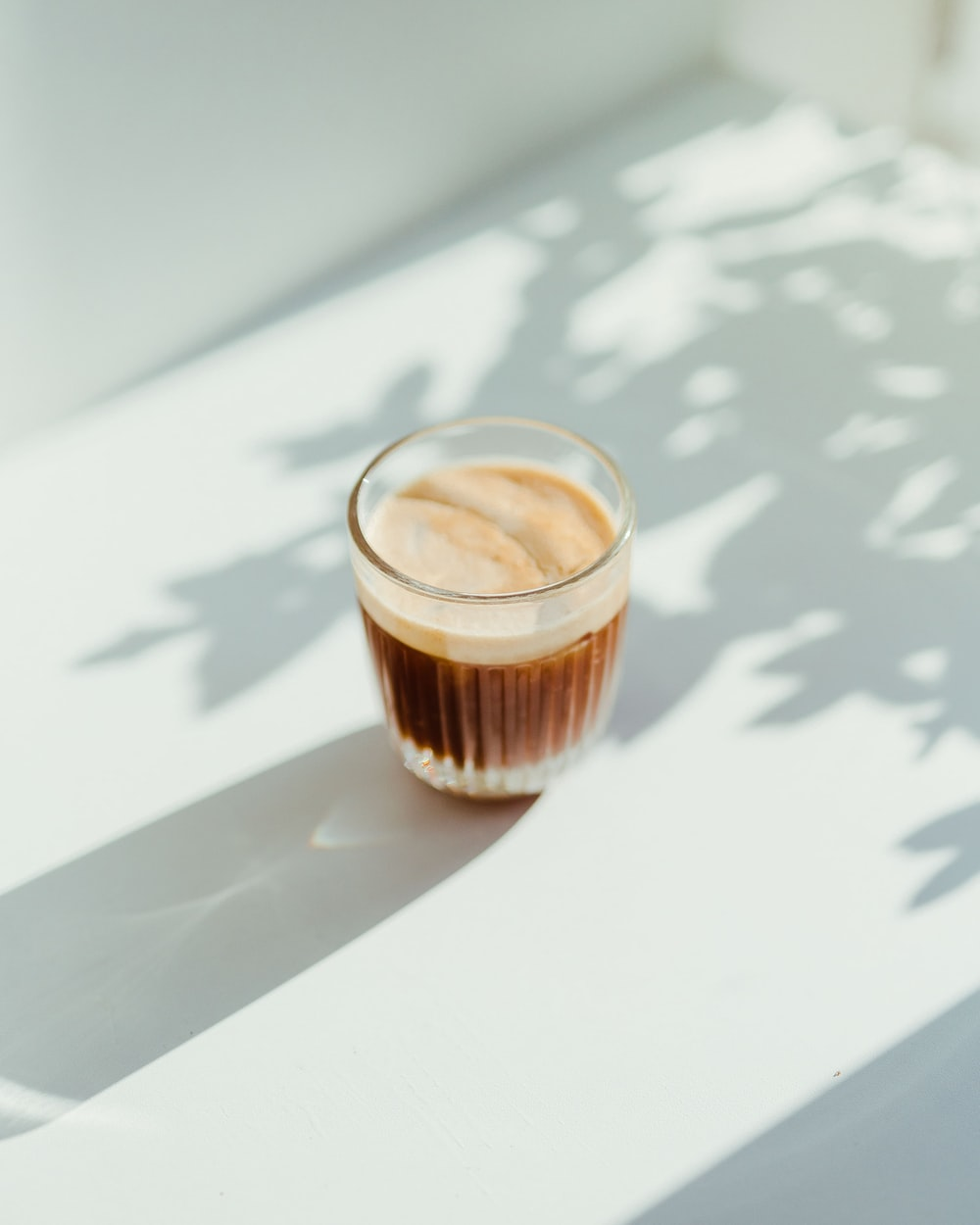 clear drinking glass with coffee on top of white table
