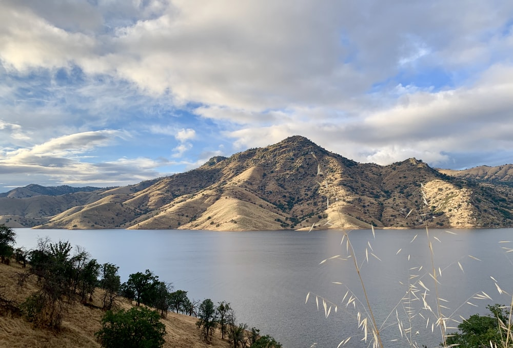 soil mountains and lake during day