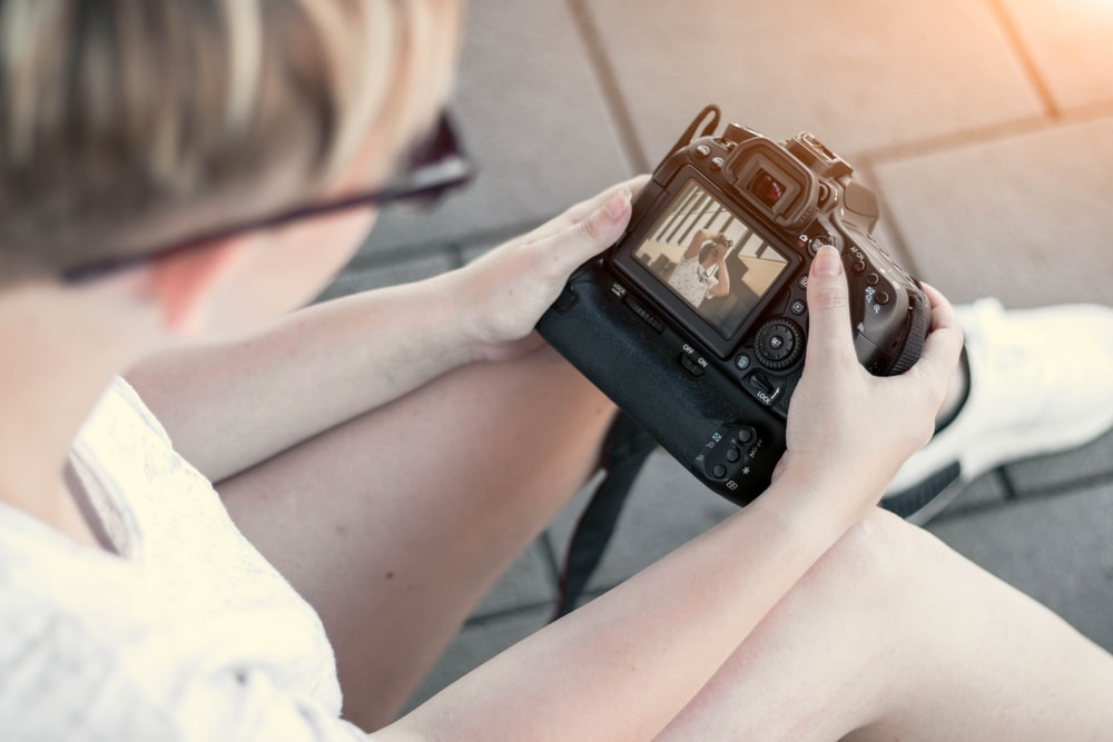 person showing photo from a DSLR camera