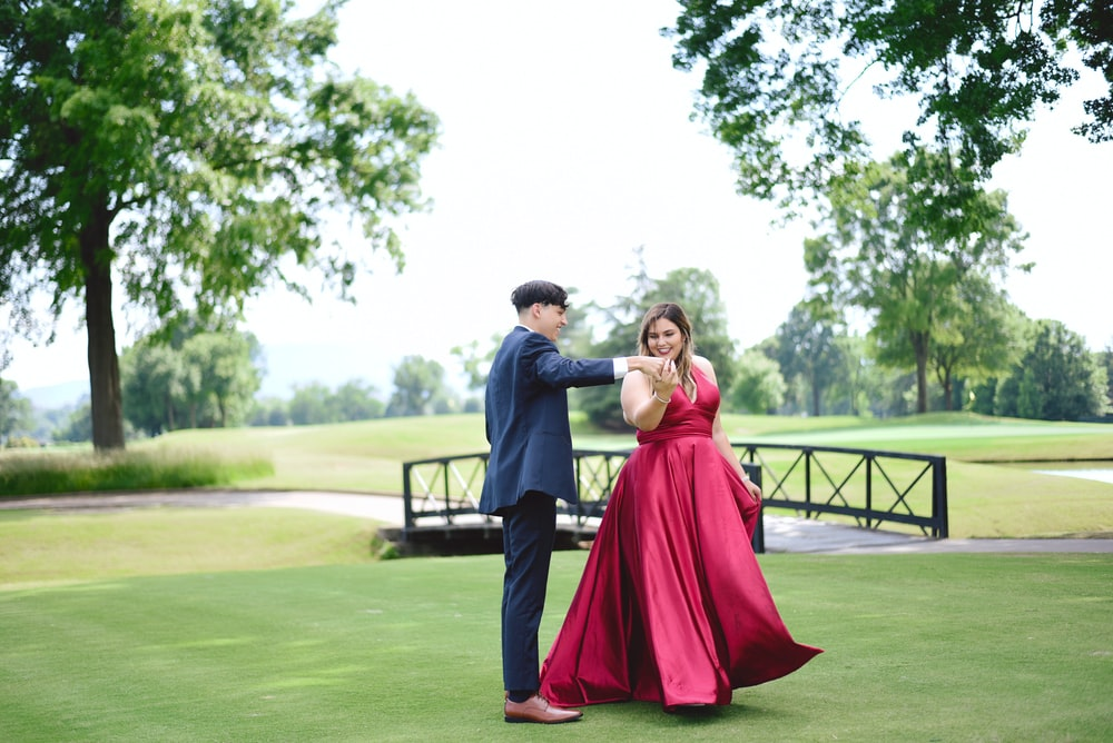 man in grey suit dancing with woman wearing pink dress outside