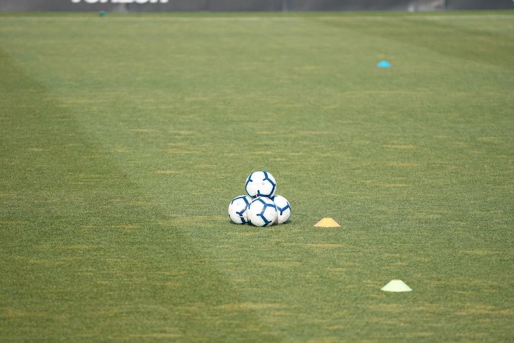 pile of white-and-blue soccer balls