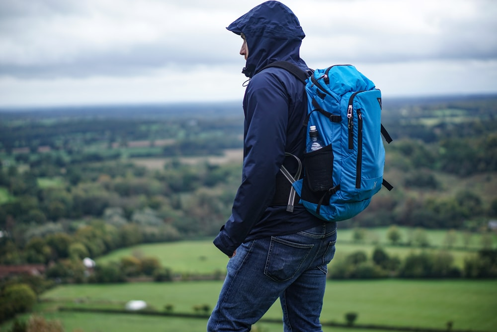 man wearing purple hoodie standing on hill carrying blue backpack