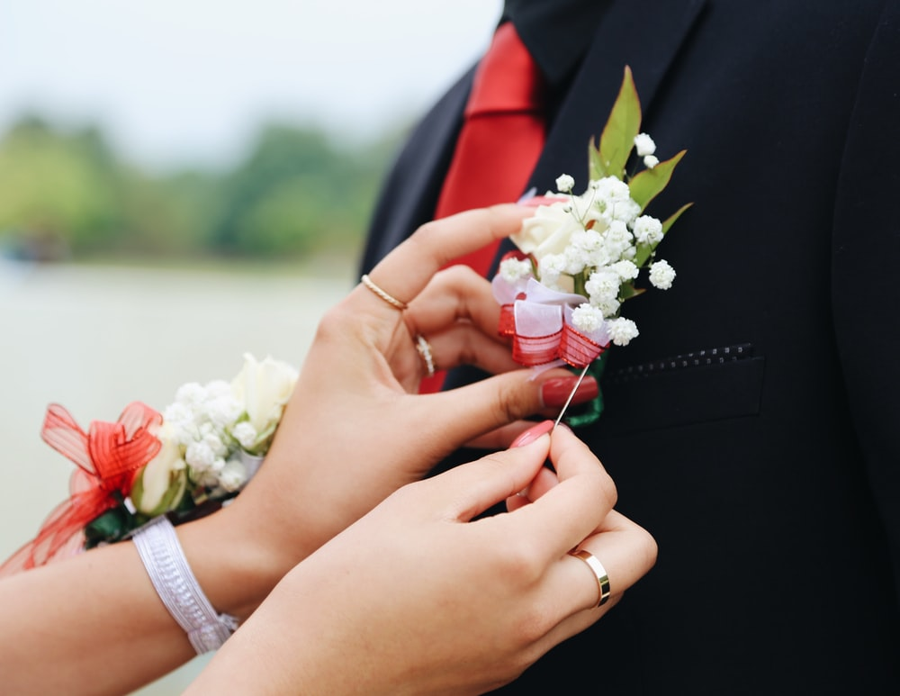 woman putting white flower on man's suit