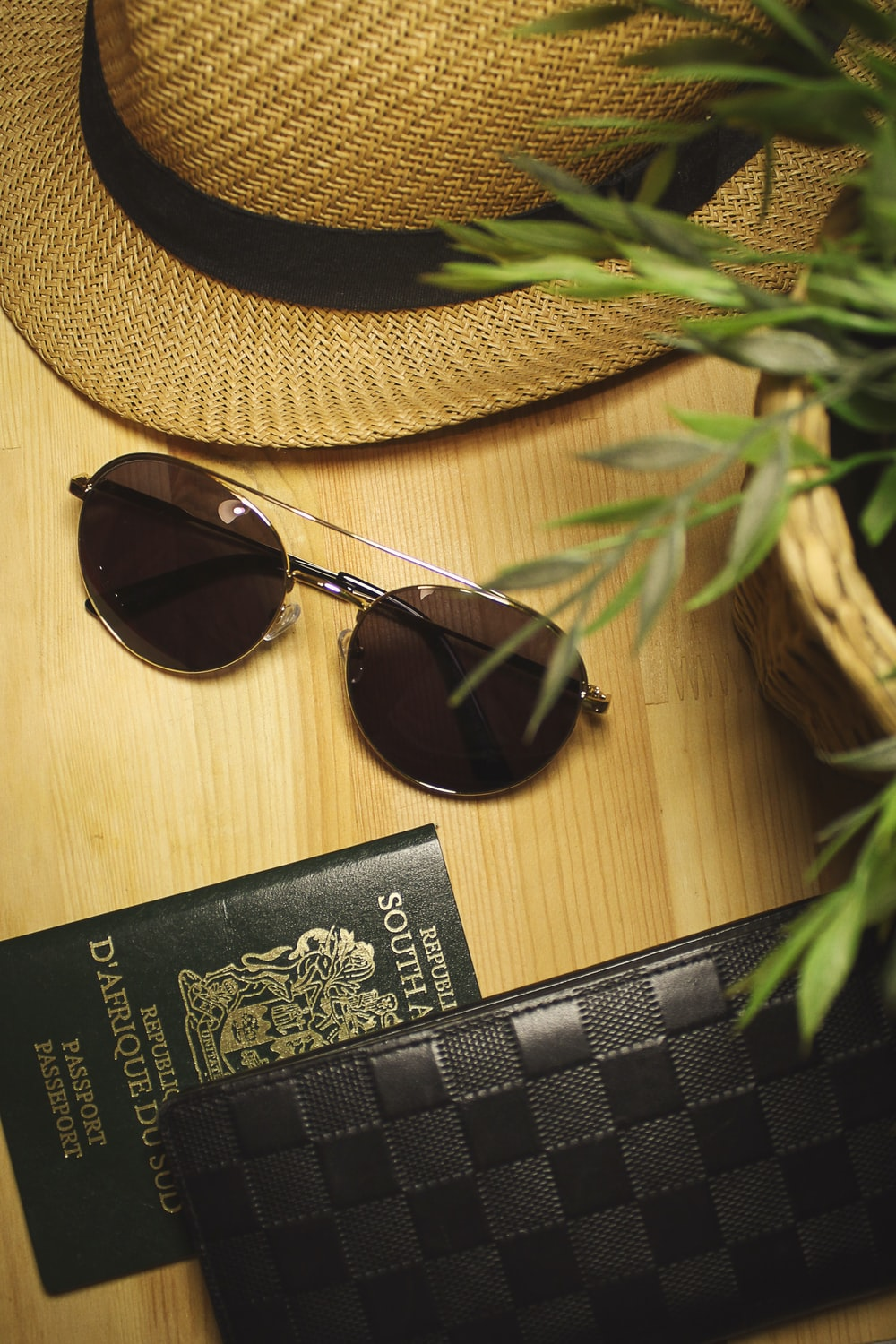 black Louis Vuitton leather wallet beside passport and sunglasses