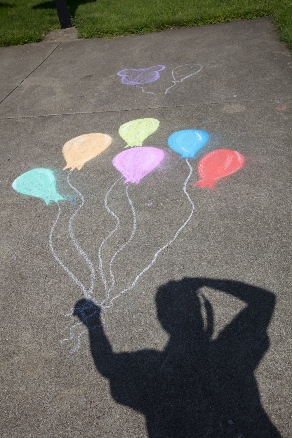 person's shadow holding bundle of balloons chalk art on concrete ground
