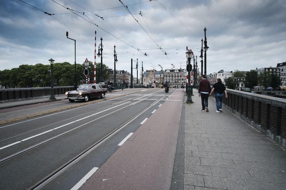 two persons walking along sidewalk of bridge